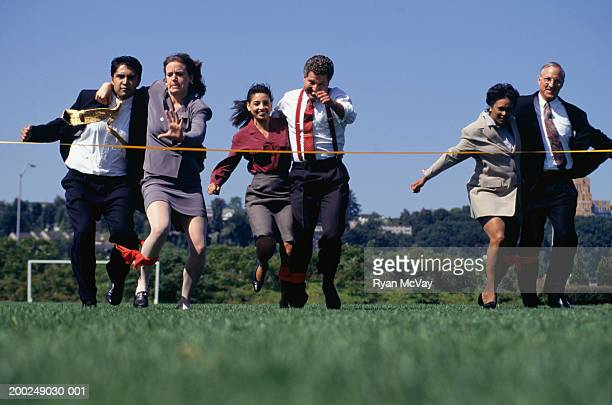 6 businesspeople in three-legged race