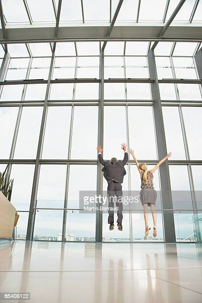 Businesspeople jumping in modern lobby
