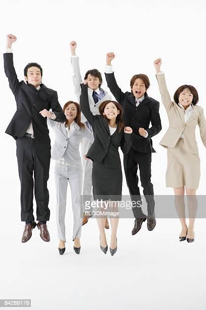 Businesspeople jumping, raising fists, studio shot