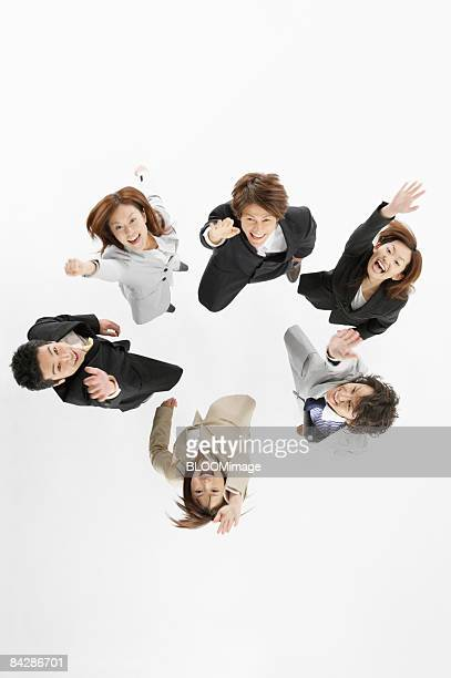 Businesspeople jumping, raising hands, view from above, studio shot