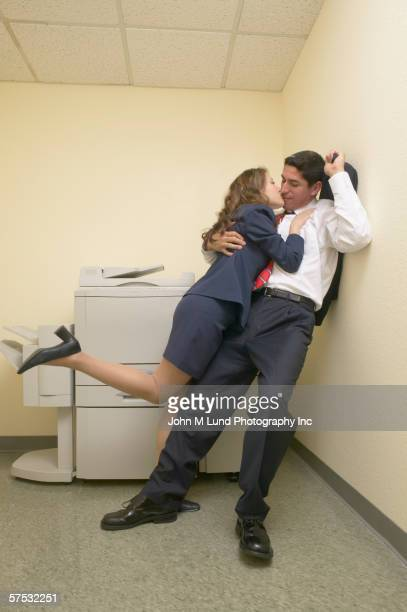 Businesspeople kissing by copy machine