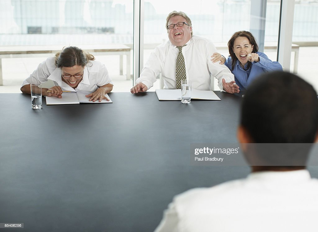 Businesspeople laughing at applicant in interview : Stock Photo