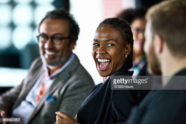 businesspeople laughing at conference - colleague stock pictures, royalty-free photos & images