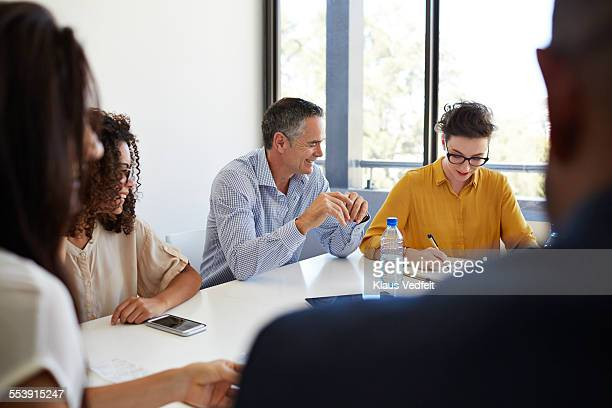 Businesspeople laughing at meeting
