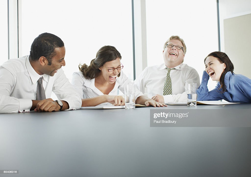 Businesspeople laughing in conference room : Stock Photo