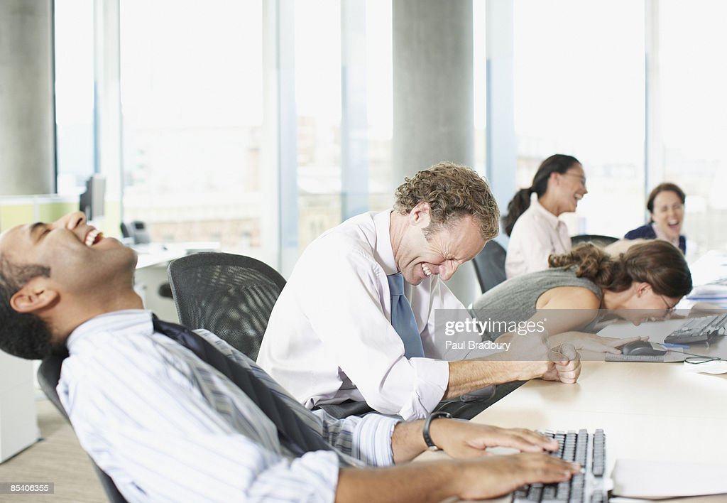 Businesspeople laughing in office : Stock Photo