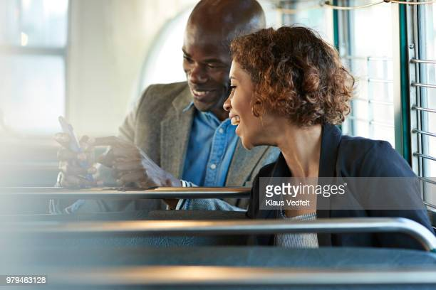 Businesspeople laughing & looking at smartphone, while riding tram