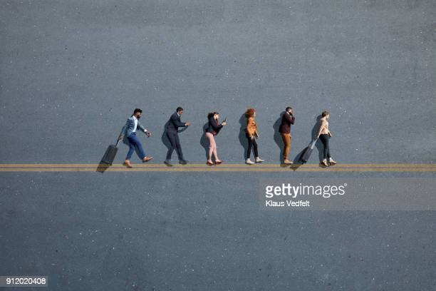 Businesspeople laying in line, with suitcases and phones, on painted asphalt with double line