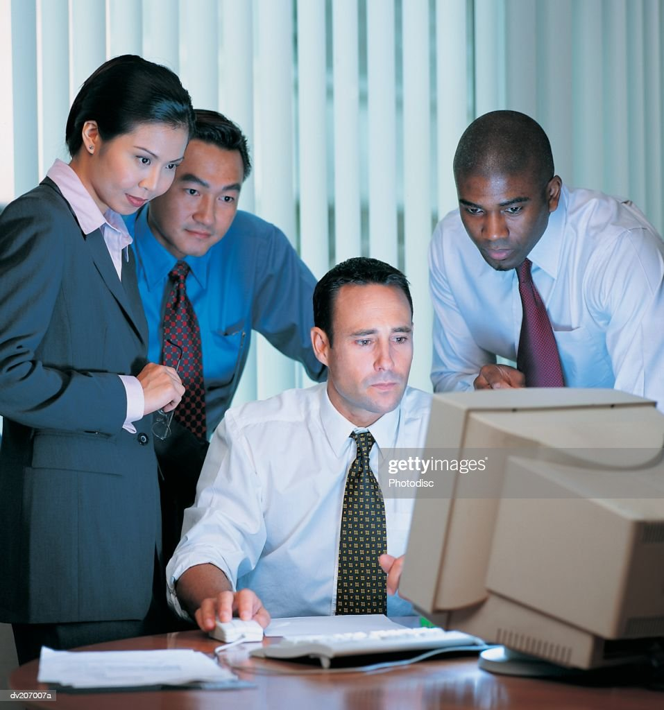 Businesspeople looking at computer monitor : Stock Photo