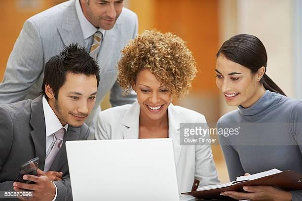 businesspeople looking at laptop computer - oliver eltinger stock-fotos und bilder