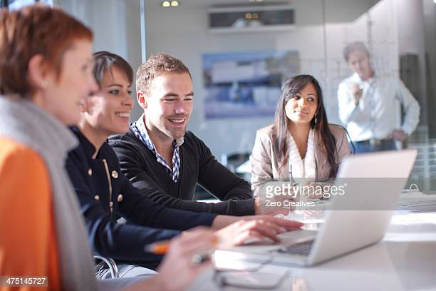 Businesspeople looking at laptop computer, smiling