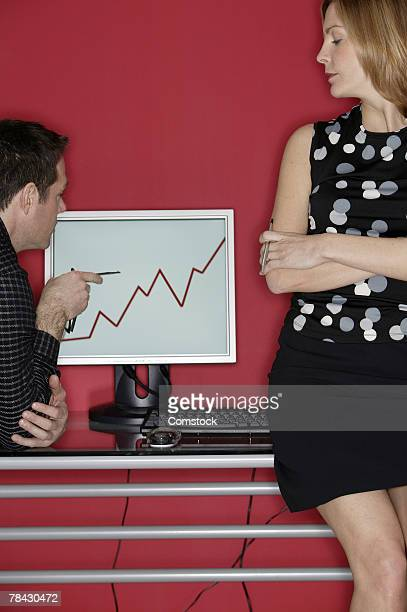 Businesspeople looking at line graph on computer monitor