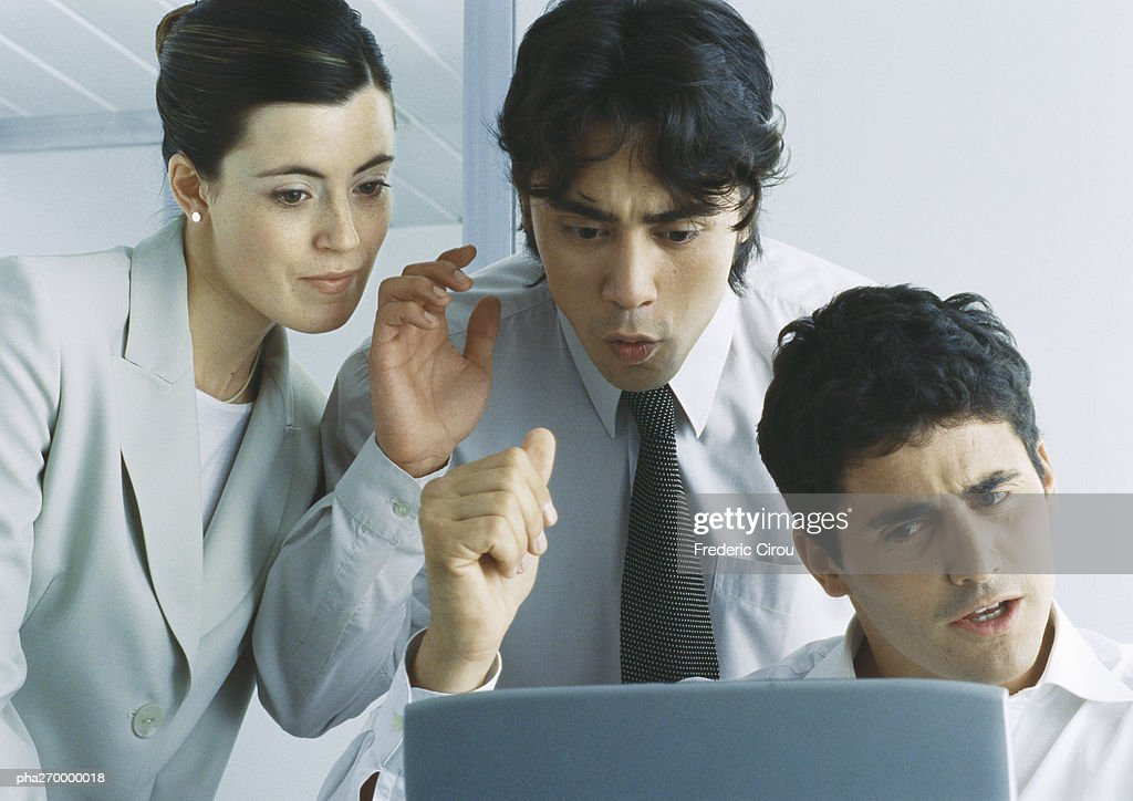 Businesspeople looking down at computer screen gesturing and making faces : Stockfoto