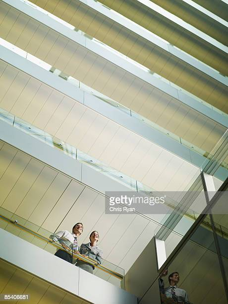 businesspeople looking over balcony in atrium - building atrium stock pictures, royalty-free photos & images
