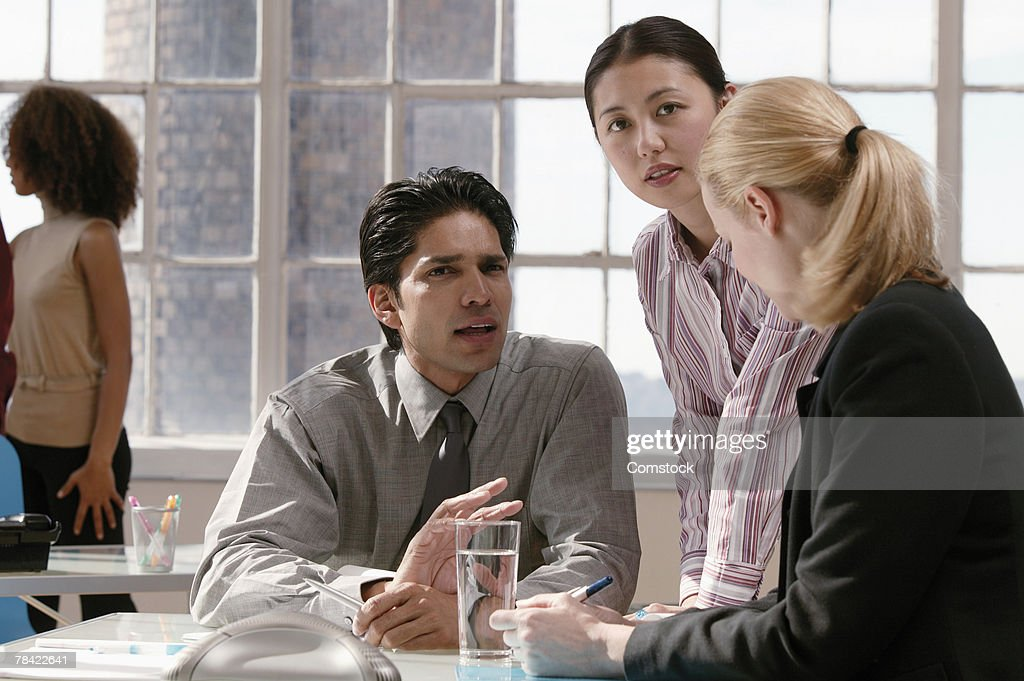 Businesspeople looking up from conversation : Stock Photo
