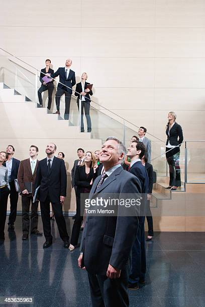 Businesspeople looking up in office lobby