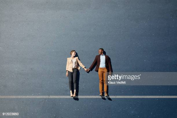 Businesspeople lying down and holding hands, with line painted on asphalt