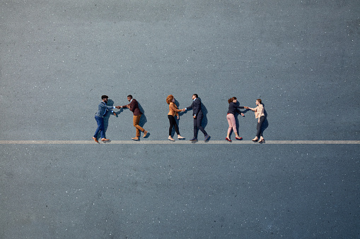 Businesspeople lying down and shaking hands on line, painted on asphalt - gettyimageskorea