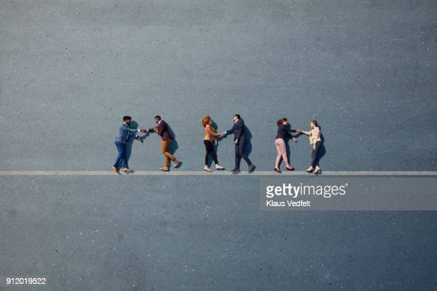 Businesspeople lying down and shaking hands on line, painted on asphalt