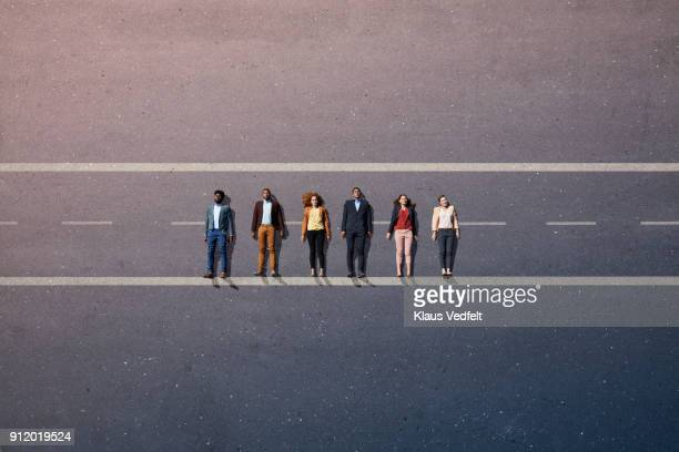 Businesspeople lying down on road, painted on asphalt