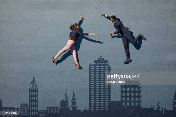 Businesspeople lying on painted asphalt with skyline. Trying to embrace each other
