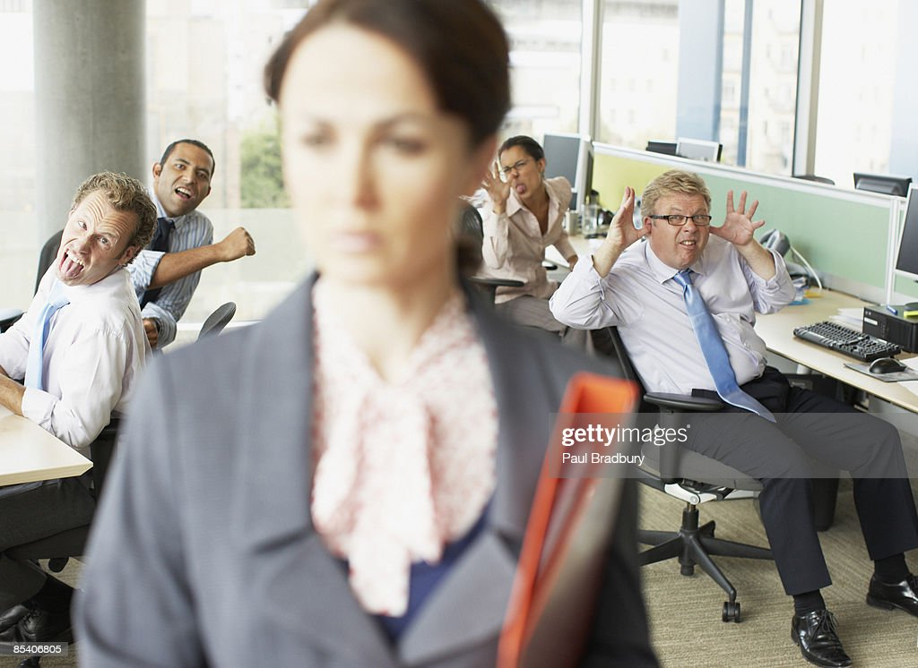 Businesspeople making face at boss in office : Stock Photo