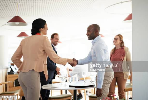 businesspeople making handshakes, at restaurant - leanincollection stock photos and pictures