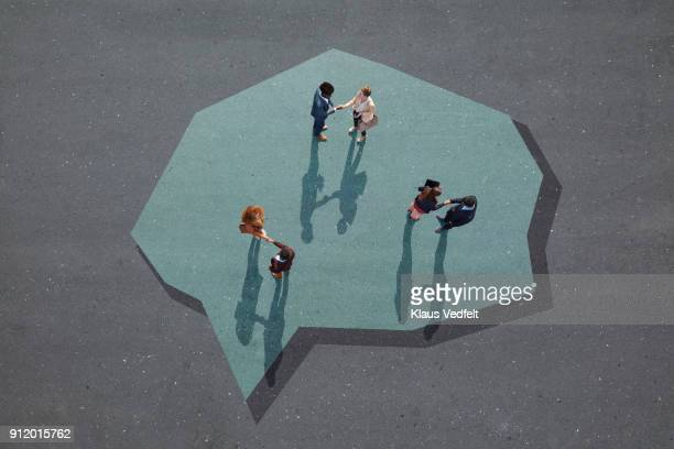 Businesspeople making handshakes, inside big painted speech bubble on asphalt