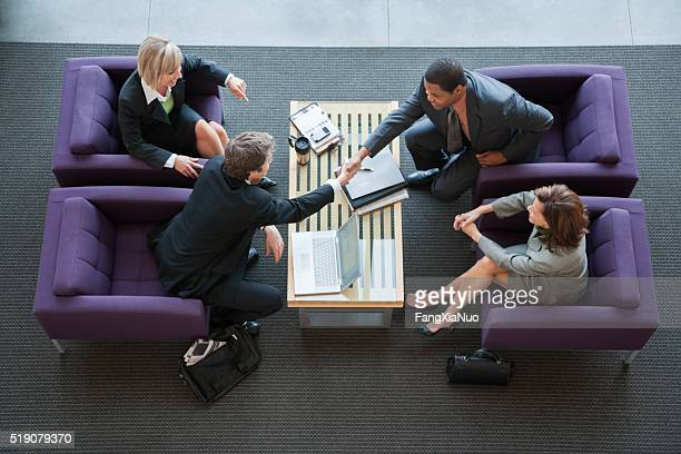 businesspeople making introductions - vier personen stockfoto's en -beelden