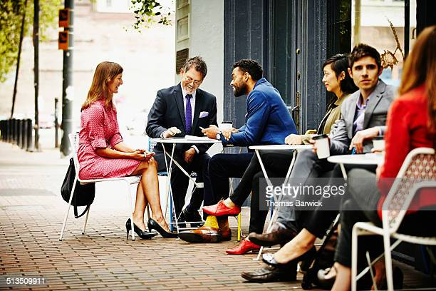 businesspeople meeting at outdoor table of cafe - leanintogether stock pictures, royalty-free photos & images