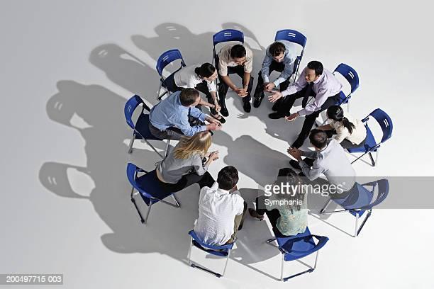 businesspeople meeting in circle, leaning forward, elevated view - cadeira dobrável - fotografias e filmes do acervo