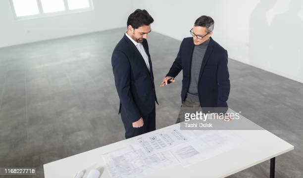businesspeople meeting to look at plans in empty office - real estate developer stock pictures, royalty-free photos & images