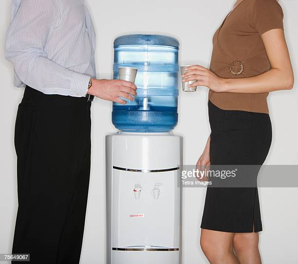 businesspeople next to water cooler - water cooler stock photos and pictures