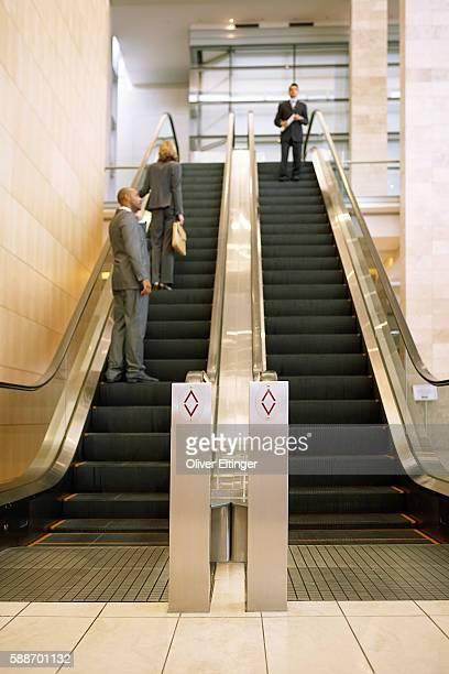 businesspeople on escalators - oliver eltinger stock-fotos und bilder
