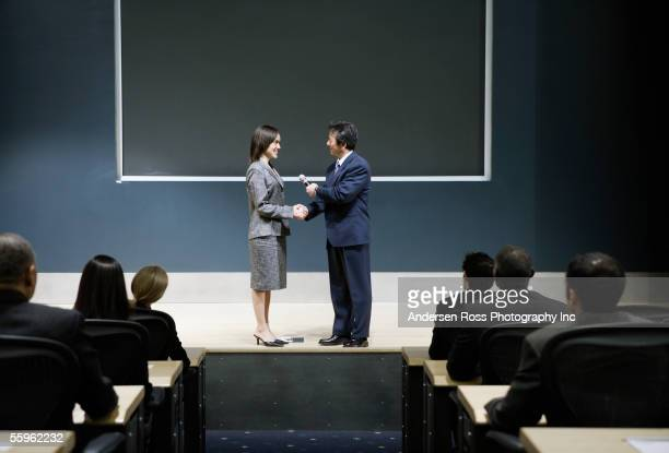 Businesspeople on stage shaking hands