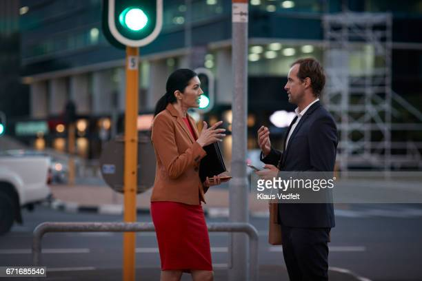 Businesspeople on street talking together, at night