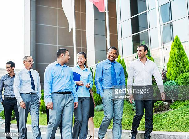 Businesspeople outside walking in front of office building.
