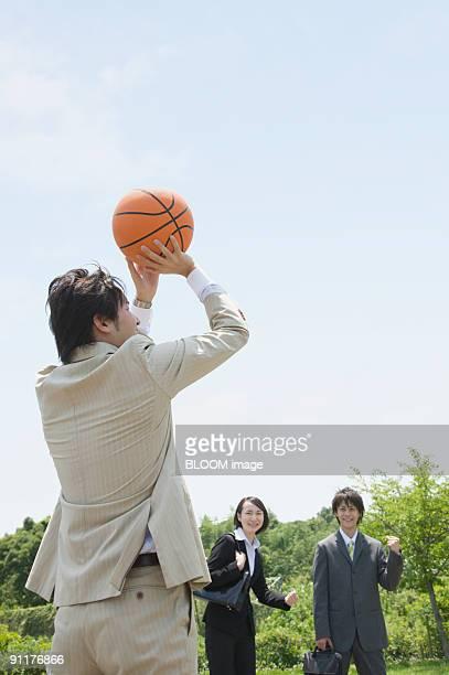Businesspeople playing basketball