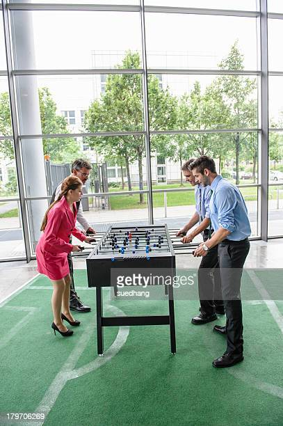 Businesspeople playing table football in lobby