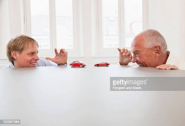 Businesspeople playing with toy cars