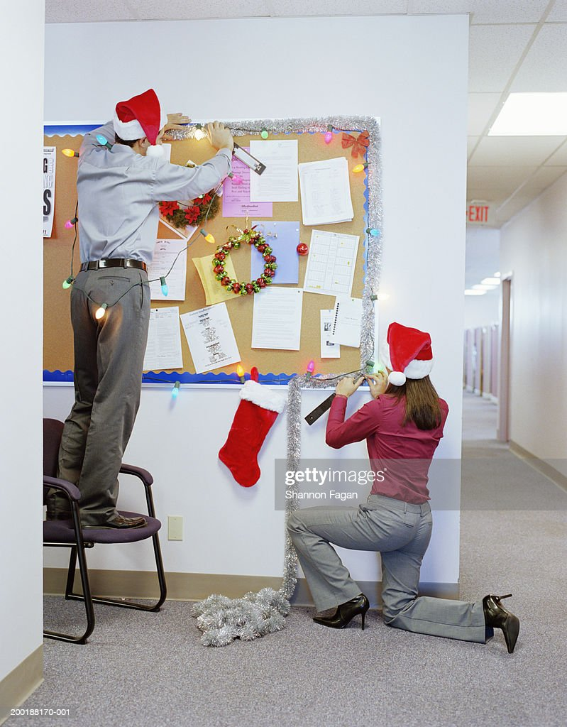 christmas decoration office. Businesspeople Putting Up Christmas Decorations In Office, Rear View : Stock Photo Decoration Office