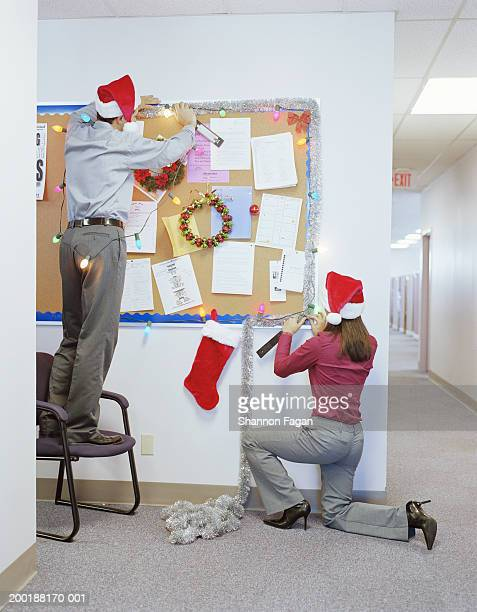 businesspeople putting up christmas decorations in office, rear view - men wearing stockings stock pictures, royalty-free photos & images