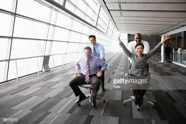 businesspeople racing on office chairs - sedia da ufficio foto e immagini stock
