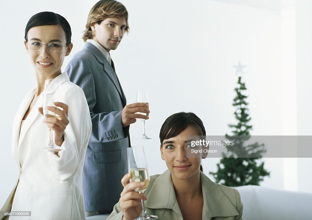 Businesspeople raising champagne flutes with christmas tree in background : Stockfoto