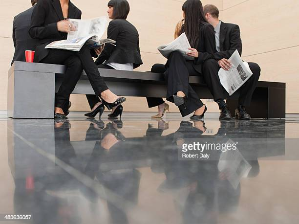 businesspeople reading newspapers on office bench - lingering stock pictures, royalty-free photos & images