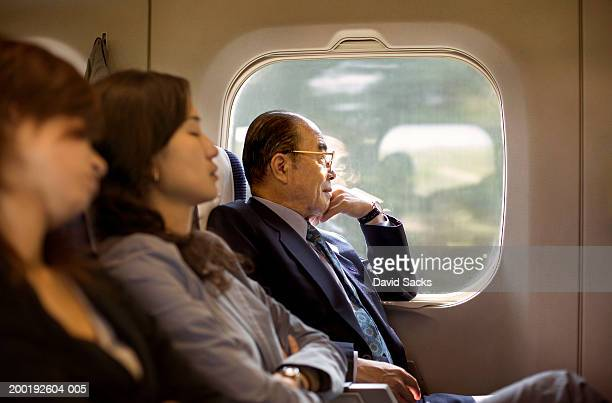 Businesspeople riding on train, side view (focus on senior man)