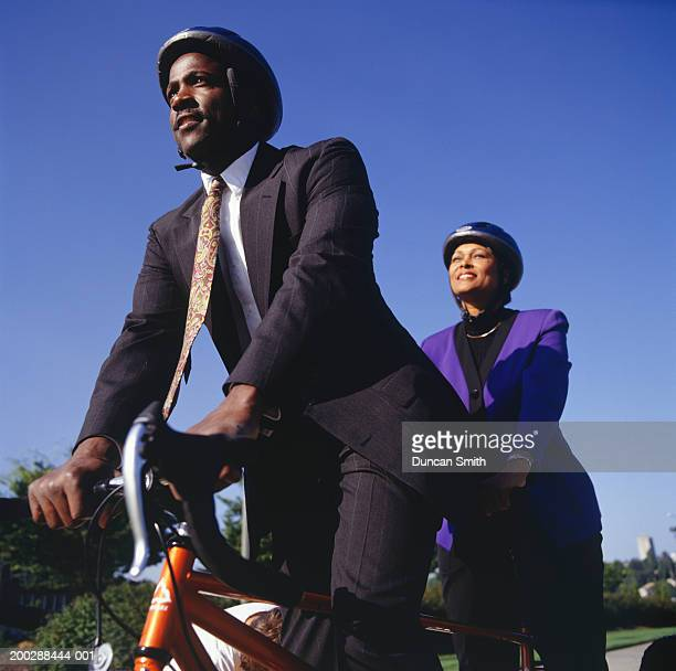 Businesspeople riding tandem bicycle on path, low angle view