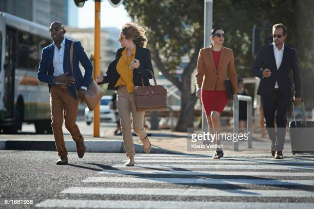 Businesspeople running in pedestrian crossing with phones and bags