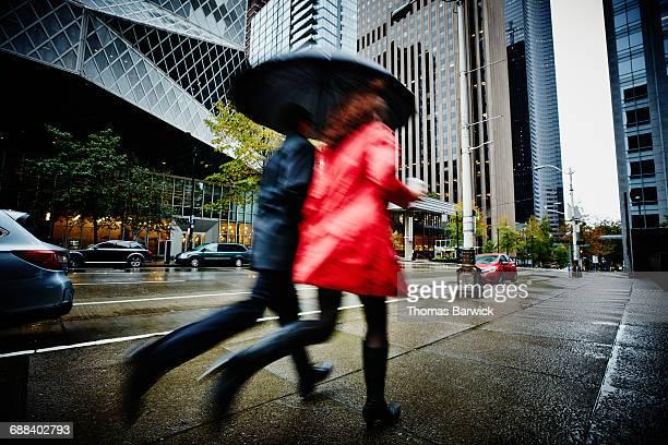 Businesspeople running on city sidewalk