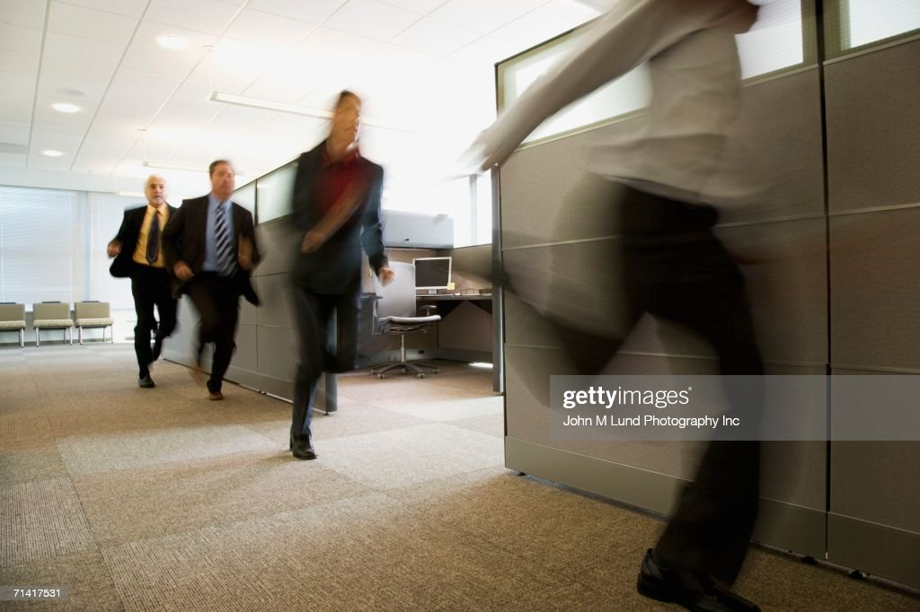 Businesspeople running past office cubicles : Stock Photo